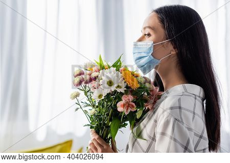 Side View Of Young Allergic Woman In Medical Mask Holding Flowers At Home