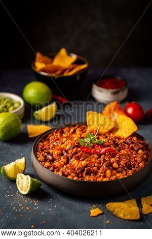 Mexican Hot Chili Con Carne In A Bowl With Tortilla Chips On Dark Background
