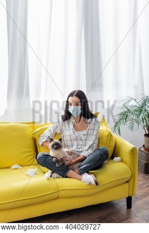 Young Allergic Woman In Medical Mask Suffering From Allergy While Sitting On Sofa With Cat And Crump