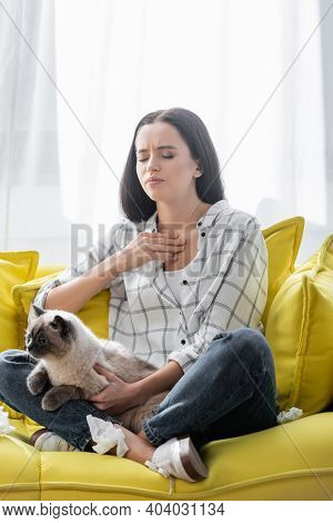 Allergic Woman With Closed Eyes Touching Throat While Sitting On Couch With Cat
