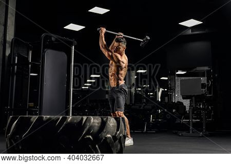 Side View Of Powerful Muscular Man Hitting Giant Tire With Sledgehammer. Motion Of Shirtless Bearded