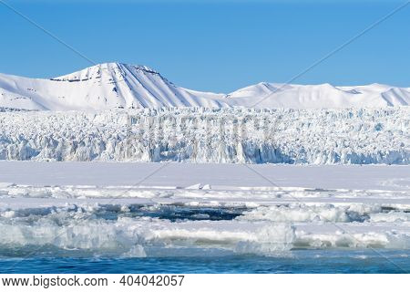 View of a glacier and pristine snow covered mountains in Nordfjorden, Svalbard, a Norwegian archipelago between mainland Norway and the North Pole