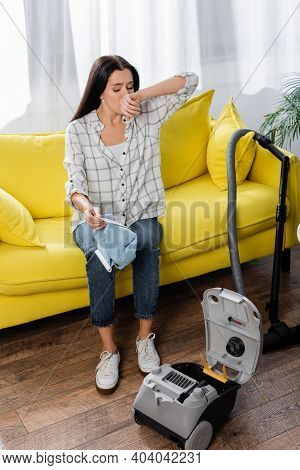 Allergic Woman Wiping Nose While Sitting On Sofa With Vacuum Cleaner Dust Bag