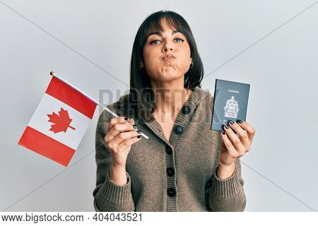 Young hispanic woman holding canada flag and passport puffing cheeks with funny face. mouth inflated with air, catching air.