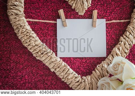 A Braided Heart-shaped Frame With A Card For Labeling On The Clothespins On A Crimson Background