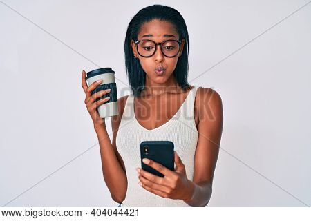 Young african american woman holding takeaway cup of coffee using smartphone puffing cheeks with funny face. mouth inflated with air, catching air.