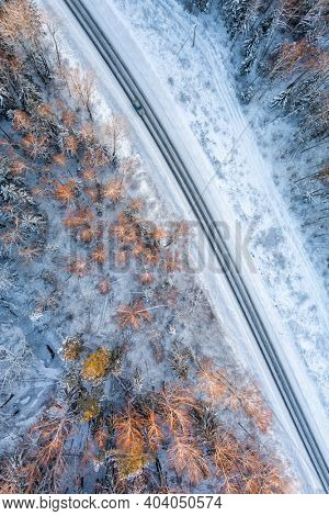 Aerial view from drone of car on curvy snow covered road in the winter forest