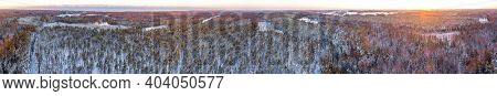 Snow covered winter forest view from drone during sunrise