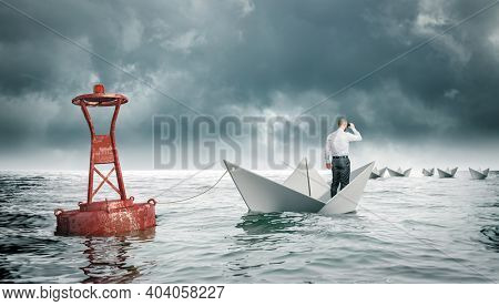 man with binoculars on paper boat tied to a buoy. boats that go away. concept of aspiration and adversity.