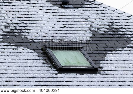 A Vertical Portrait Of A Frozen Slate Roof With A Skylight Window Which Is Also Frozen During Winter