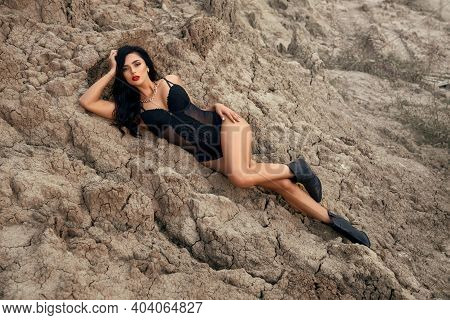 Impressive Young Woman With Long Wavy Hair Lying On Dry Sand In Quarry. Attractive Female Model Wear