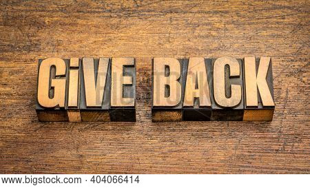 give back - words in vintage letterpress wood type against rustic wooden background, generosity and repay concept