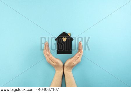 Woman's Hands Surround A Mock-up Of A Dark House On A Blue Background. Family, Real Estate And Insur