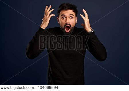 Horizontal Shot Of Stupefied Stunned Shocked Bearded Young Male Keeps Mouth Widely Opened, Being Sur