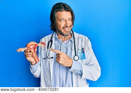 Middle age handsome gynecologist man holding anatomical model of female genital organ smiling happy pointing with hand and finger