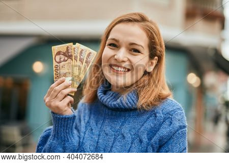 Young caucasian girl smiling happy holding hungarian forint banknotes at the city.