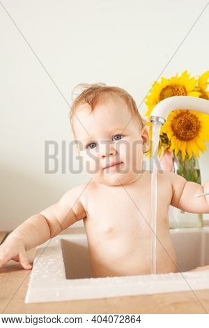 Baby Taking Bath In Kitchen Sink. Little Boy Bathing. Water Fun For Kids. Hygiene And Skin Care For