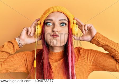 Young caucasian woman listening to music using headphones puffing cheeks with funny face. mouth inflated with air, catching air.