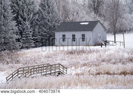 Winter Wonderland Scene In Rural Minnesota With A Bridge, Cattails And An Old Fashioned Barn