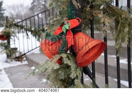 Glittery Red Christmas Bell Decorations With Pine Garland, Attached To An Iron Fence