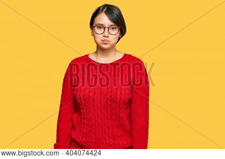 Young beautiful hispanic woman with short hair wearing casual sweater and glasses puffing cheeks with funny face. mouth inflated with air, crazy expression.