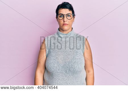 Plus size brunette woman wearing casual clothes and glasses with serious expression on face. simple and natural looking at the camera.
