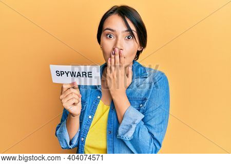 Beautiful young woman with short hair holding spyware text covering mouth with hand, shocked and afraid for mistake. surprised expression