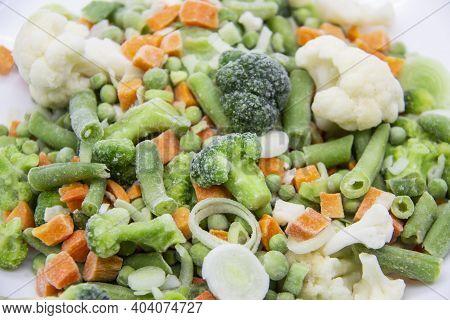 Frozen Vegetables: Cauliflower, Green Peas, Leeks, Broccoli, Carrots, Green Beans On A White Plate.
