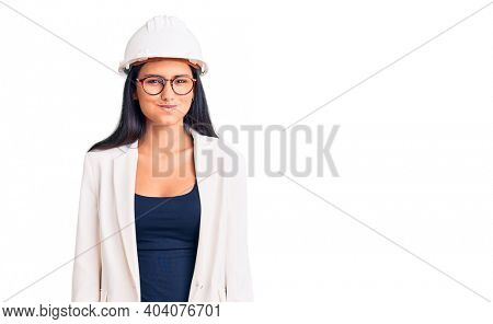 Young beautiful latin girl wearing architect hardhat and glasses puffing cheeks with funny face. mouth inflated with air, crazy expression.