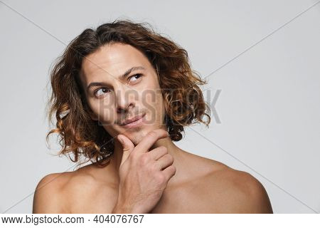 Perplexed shirtless guy thinking and looking upward isolated over white background