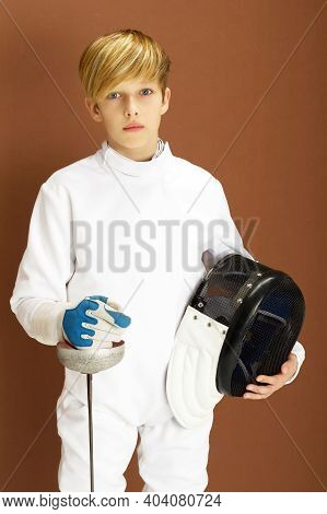 Boy Fencer In White Fencing Costume With Rapier. Closeup Portrait Of Teenage Boy Wearing White Fence
