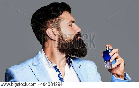 Masculine Perfume, Bearded Man In A Suit. Male Holding Up Bottle Of Perfume. Perfume Or Cologne Bott