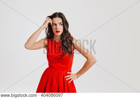 Perplexed beautiful brunette girl thinking and looking upward isolated over white background
