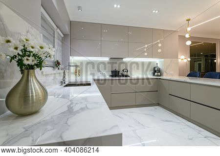 Closrup of luxury large modern white marble kitchen united with dining room
