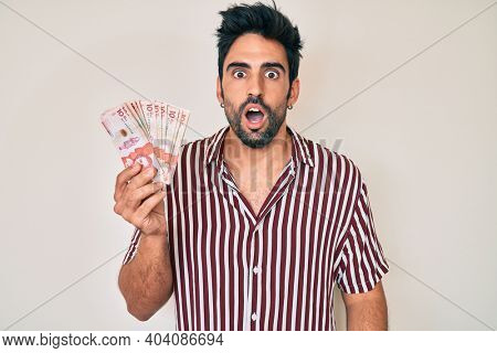 Handsome hispanic man with beard holding colombian pesos scared and amazed with open mouth for surprise, disbelief face