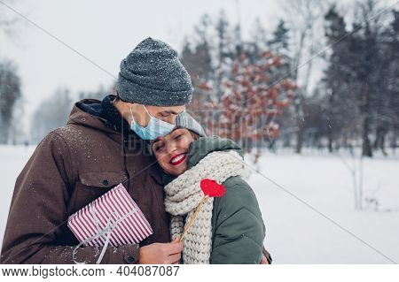 Couple In Love Hugs With Presents In Snowy Winter Park On Valentines Day. Red Lipstick Mark On Mans
