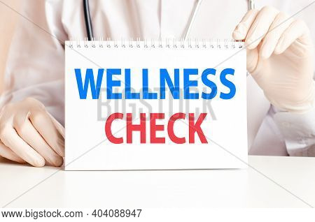 Wellness Check Card In Hands Of Medical Doctor. Doctor's Hands In Gloves Holding A Sheet Of Paper Wi