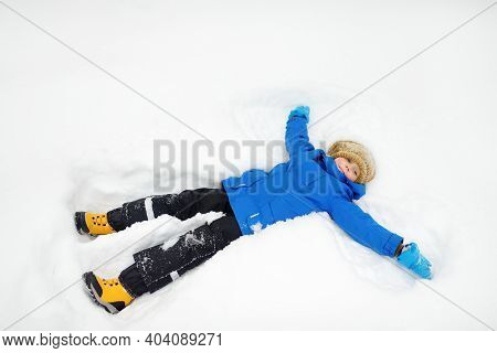 Top View Of Child Doing Snow Angel. Little Boy Playing In Snowdrift And Having Fun With Fresh Snow.