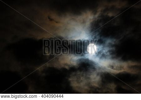 The Full Moon Hiding In The Cloudy Night Sky. Dark Background Of The Moonlight And Clouds