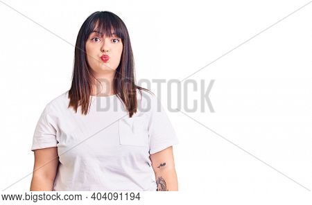 Young plus size woman wearing casual clothes puffing cheeks with funny face. mouth inflated with air, crazy expression.