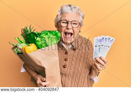Senior grey-haired woman holding groceries and colombian pesos banknotes smiling and laughing hard out loud because funny crazy joke.