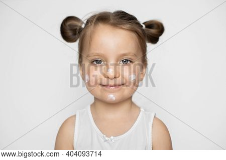 Close Up Of Funny Cheerful Little 3 Years Old Blond Haired Caucasian Girl In White Shirt With Cream