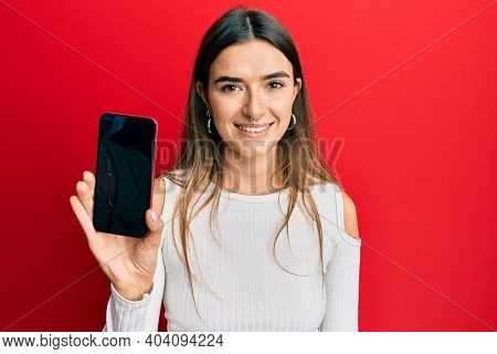 Young hispanic woman holding smartphone showing blank screen looking positive and happy standing and smiling with a confident smile showing teeth