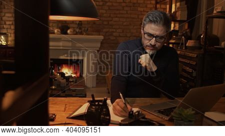 Home office - older white man working from home. Thinking, typing on laptop computer. Sitting at desk in dark living room iin front of fireplace.