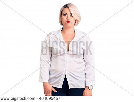 Young blonde plus size woman wearing casual shirt puffing cheeks with funny face. mouth inflated with air, crazy expression.