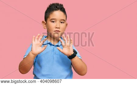 Little boy hispanic kid wearing casual clothes moving away hands palms showing refusal and denial with afraid and disgusting expression. stop and forbidden.