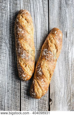Two crispy fresh baguettes on a wooden table. Top view.