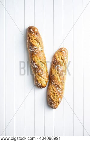 Two crispy fresh baguettes on a white table. Top view.