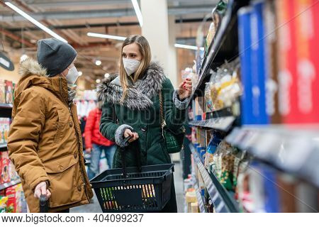 Family shopping in supermarket during covind19 pandemic standing at shelf