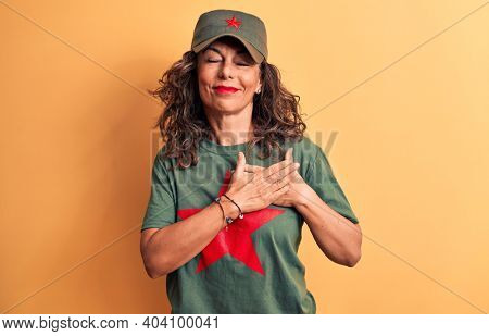 Middle age brunette woman wearing t-shirt and cap with red star symbol of communism smiling with hands on chest, eyes closed with grateful gesture on face. Health concept.